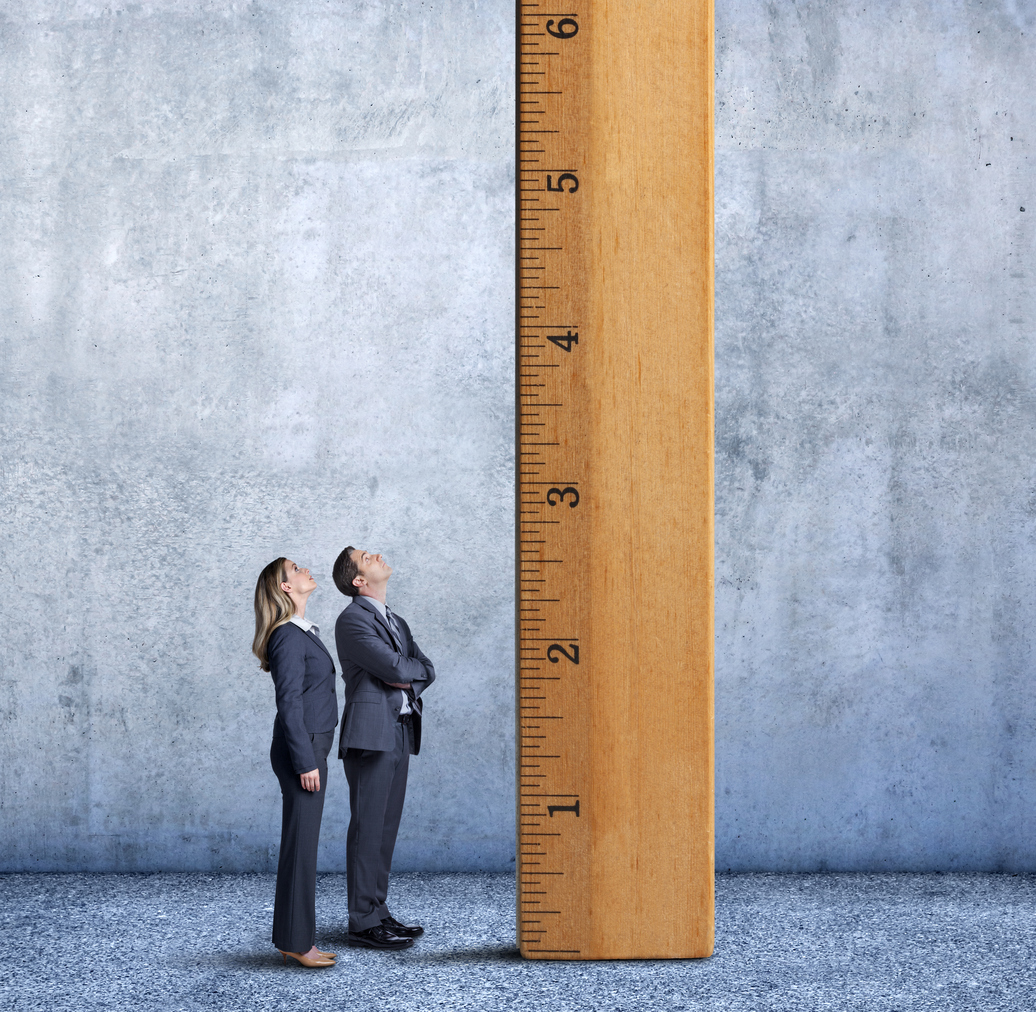 A businesswoman and businessman stand at a profile to the camera as they looks up at a large wooden ruler that is standing on its end inside a large room.
