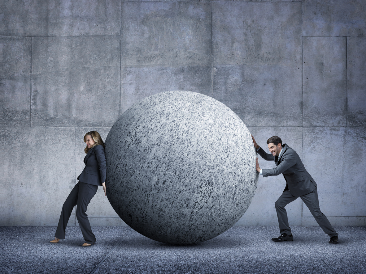 A businessman and a businesswoman working against each other while trying to move a large sphere as they both push against each other.