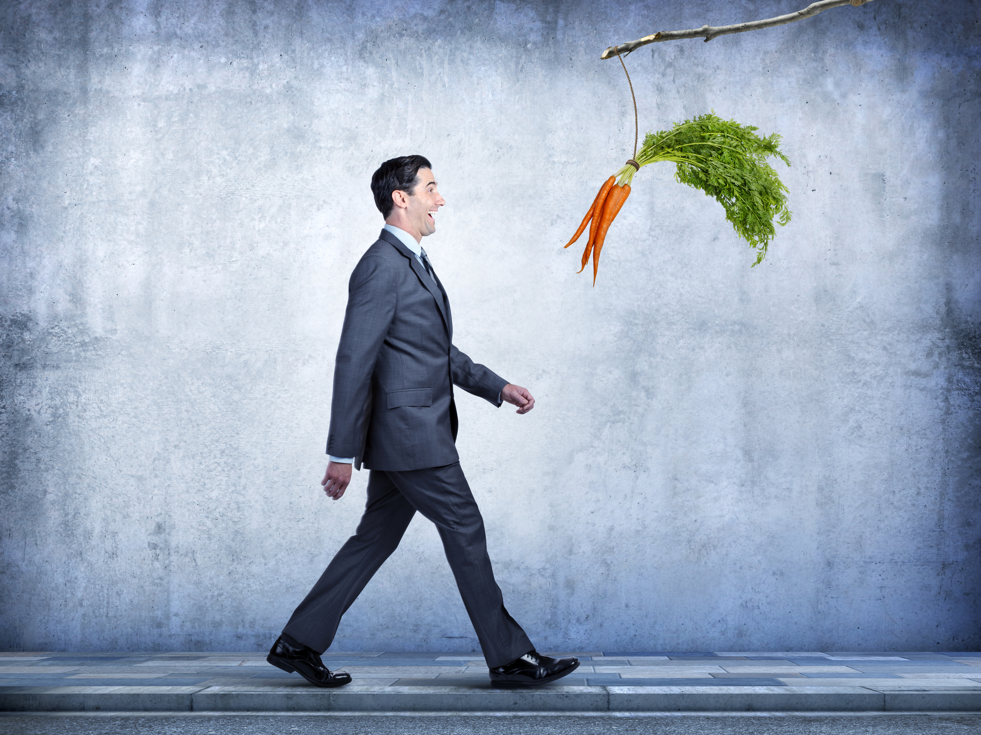 A businessman, walking along a sidewalk, happily follows a bunch of carrots that are dangling from a stick. The carrots are his motivation as he works his way through his day.