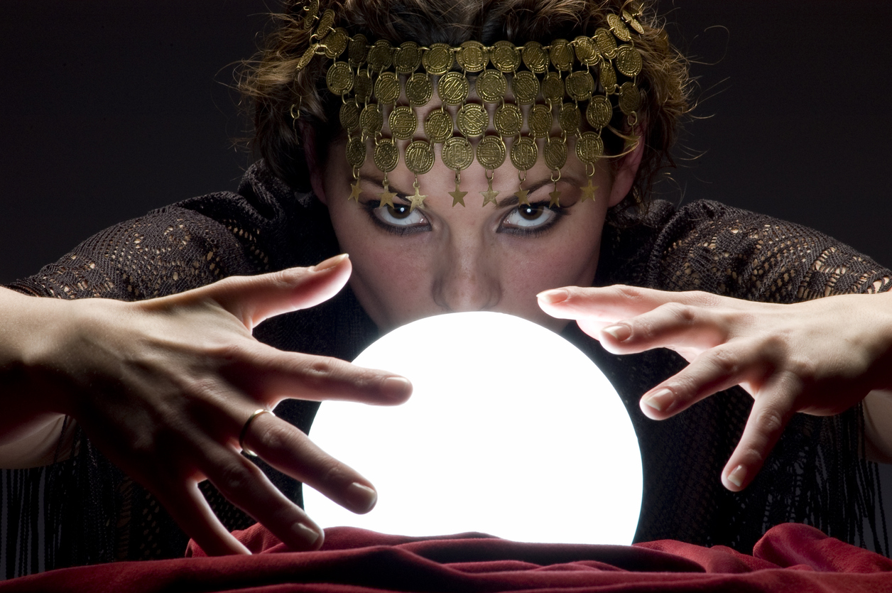 Close up of mysterious focused fortune telling woman wearing a copper hair dress with her hands on a glowing crystal ball looking at the camera